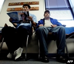 FILE - A Salvadoran national, left, accompanied by a friend, waits in the lobby of the Comite Hispano de Virgina, in Falls Church, Virginia, Nov. 11, 2002, to get help with his US immigration paperwork to extend his Temporary Protected Status (TPS).
