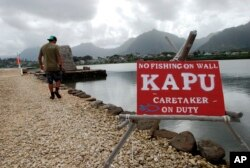 FILE - Conservation International's Luka Mossman, who restores and researches Native Hawaiian fishponds, walks along a barrier wall on Heeia fishpond in Kaneohe, Hawaii, Dec. 2, 2016.