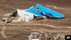 In this photo made available Nov. 2, 2015, and provided by Russian Emergency Situations Ministry, Egyptian military forces approach a plane's tail at the wreckage of a passenger jet bound for St. Petersburg in Russia that crashed in Hassana, Egypt.