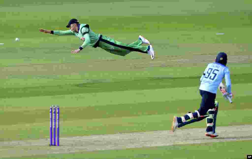Ireland's Harry Tector, left, dives to make a catch but misses, during the third One Day International cricket match between England and Ireland, at the Ageas Bowl in Southampton, England.