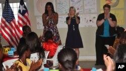 Michelle Obama (depan berdiri paling kiri) bersama para siswi sekolah di Kakata, Liberia, Senin (27/6).