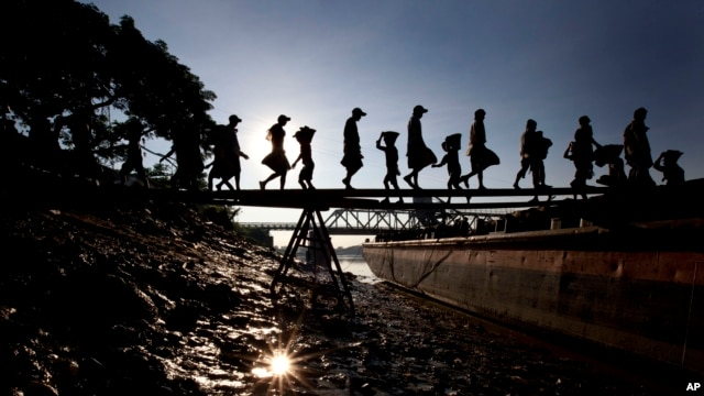 Unskilled workers unload pebbles form a tug boat in Rangoon, Burma, November 23, 2012.