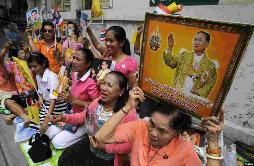 People hold portraits of Thailand's King Bhumibol Adulyadej as they wait for him to leave Siriraj hospital in Bangkok, August 1, 2013.