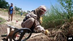 FILE - A de-miner searches for mines in Bagram, north of Kabul, Afghanistan, June 10, 2009.