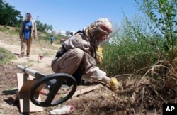 FILE - A de-miner of the Halo Trust, a British charity that specializes in the removal of land mines, searches for mines in Bagram, north of Kabul, Afghanistan, June 10, 2009.