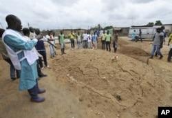 Un agent de la Croix rouge photographie une fosse commune présumée à Yopougon le 4 mai 2011