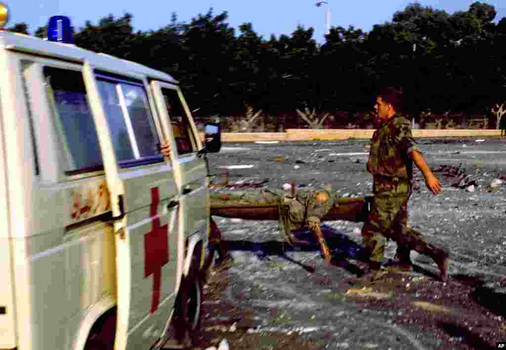 FILE - An injured service member is carried on a stretcher after a suicide truck bomb struck the U.S. Marine barracks in Beirut, Lebanon, Oct. 23, 1983.