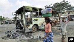 Des femmes passant devant l'épave d'un autobus incendié au quartier pro-Ouattara d'Abobo, à Abidjan