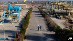 Los trabajadores caminan por un sendero en el campo de Nihran Bin Omar, al norte de Basora, a 550 kilómetros al sureste de Bagdad, el jueves 12 de enero de 2017.