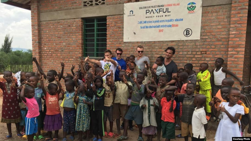 A new preschool, constructed with #BuiltWithBitcoin fundraising, brings new opportunities to youngsters in the Rwandan village of Kasebigege. Paxful CEO Ray Youssef, holding a child and not wearing sunglasses, led the fundraising effort. (Courtesy photo)