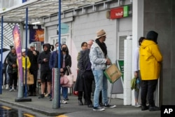 Para pelanggan antre saat akan berbelanja di sebuah supermarket di Auckland, Selandia Baru, 17 Agustus 2021.