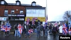 Para pendukung bendera Inggris membawa bendera di depan gedung Dewan Kota yang akan memutuskan apakah akan menurunkan bendera Inggris dari kota Belfast (4/12).