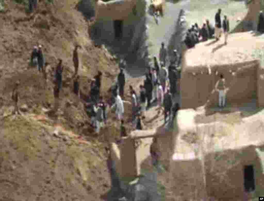 This image made from AP video shows people searching for survivors after a massive landslide landslide buried a village in Badakhshan province, northeastern Afghanistan, May 2, 2014.