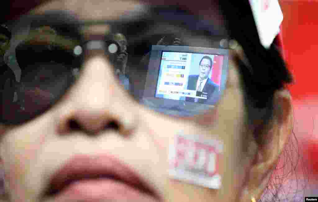 Live results are reflected in the glasses of a supporter of the Pheu Thai Party during the general election in Bangkok, Thailand, March 24, 2019.