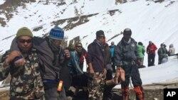 Tentara dan anggota tim penyelamatan Nepal membopong korban salju longsor di Thorong La, Nepal (17/10).