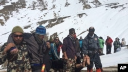 Nepalese army, rescue team members carry avalanche victims to safety at Thorong La pass area, Oct. 17, 2014.