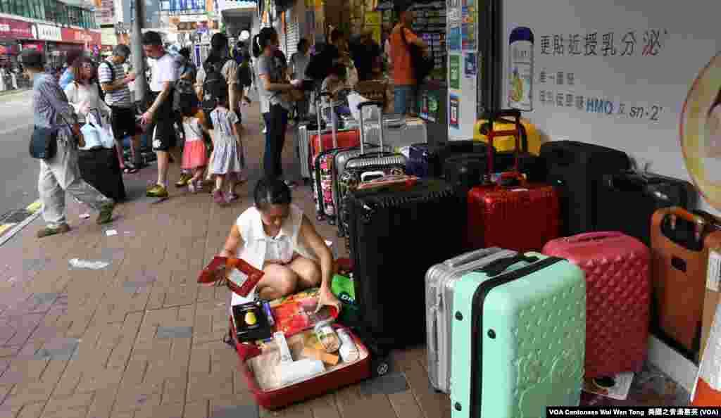 上水街頭隨處可見店舖外堆滿中國遊客及水貨客的「行李箱陣」 (美國之音湯惠芸)