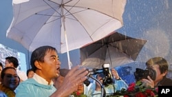 Thailand's Prime Minister Abhisit Vejjajiva speaks in the rain to supporters during final campaigning efforts for the ruling Democrat Party in Bangkok July 1, 2011. REUTERS/Sukree Sukplang (THAILAND - Tags: POLITICS ELECTIONS)