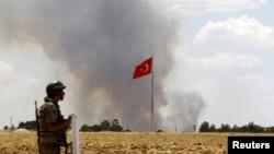 在远处的叙利亚科巴尼镇烟雾弥漫,一名土耳其士兵正在边疆看守阵地(2015年7月26日)。