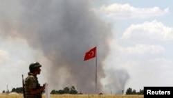 土耳其士兵守衛邊界時可看到敘利亞科巴尼鎮冒起濃煙(資料圖片)