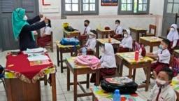 Siswa yang mengenakan masker menghadiri kelas pada hari pertama pembukaan kembali sekolah di sebuah sekolah dasar di Jakarta, Senin, 30 Agustus 2021. (Foto: AP)