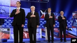 Republican presidential candidates, from left, former Pennsylvania Sen. Rick Santorum, former House Speaker Newt Gingrich, former Massachusetts Gov. Mitt Romney and Rep. Ron Paul, R-Texas, stand during the National Anthem at the Republican presidential ca