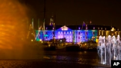 Blue Print by Dutch light designer Reier Pos is seen projected on the Nautical Museum, rear, as Arco, an art work by Austrian artist Teresa Mar is seen in the foreground, both installations are part of the Amsterdam Light Festival, Netherlands, Wednesday, Nov. 30, 2016.