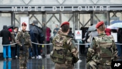 """French soldiers patrol in the courtyard of the Louvre museum with the visitor control in background in Paris, Feb. 4, 2017. The Louvre in Paris reopened to the public Saturday morning, less than 24-hours after a knife-wielding assailant shouting """"Allahu Akbar!"""" was shot by soldiers, in what officials described as a suspected terror attack."""