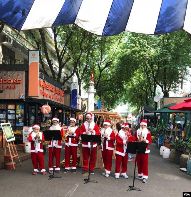 Trên Đường Sách, cũng là đường mang tên Đức TGM Nguyễn Văn Bình (1910-1995), bên hông Bưu Điện, chạy dài từ Nhà Thờ Đức Bà tới đường Hai Bà Trưng, như một tụ điểm sinh hoạt văn hoá và du lịch, đang rộn rã không khí Giáng Sinh 2017 với ban nhạc Santa Claus có lẫn cả một ông Tây béo mập cao ngồng thổi kèn, vây quanh là tấp nập khách đi xem, chụp hình, ngồi tụ tập trong các quán cà phê sách, và một số thì tìm mua sách. Đường Sách Nguyễn Văn Bình ngày nay là hình ảnh một mini-đường sách Lê Lợi của hơn 40 năm trước. [Photo tư liệu Ngô Thế Vinh]