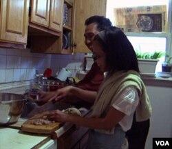 Artharini dan suami sedang sibuk menyiapkan pesanan di dapur rumah mereka di Maryland.