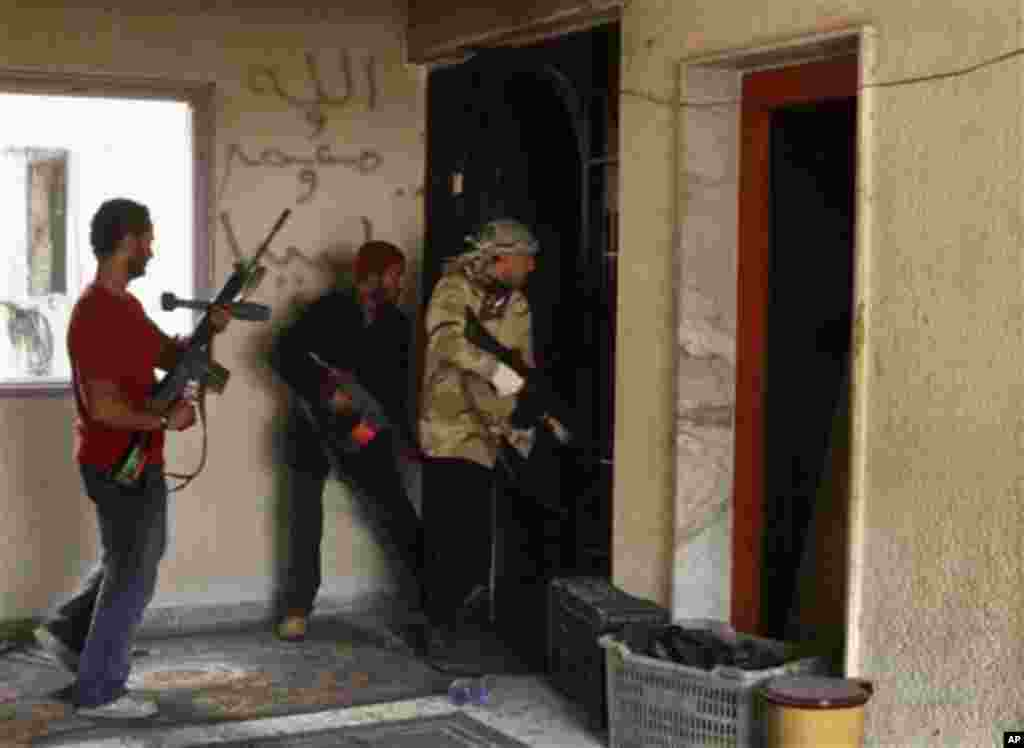 Rebel fighters search a building for pro-Gadhafi forces in the besieged city of Misrata, April 23, 2011. (AP image)