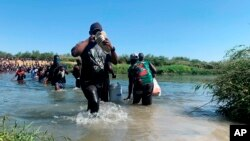 Migrants find an alternate place to cross between Mexico and the United States after access to a dam was closed, Sept. 19, 2021, in Ciudad Acuña, Mexico.