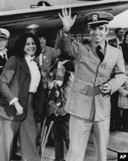 Lt. Commander John S. McCain III, a POW for over five years, waves to well wishers March 18, 1973 after arriving at Jacksonville Naval Air Station in Florida. (AP Photo)