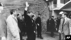 President Ronald Reagan waves just before he is shot outside the Washington Hilton on Monday, March 30, 1981. From left are secret service agent Jerry Parr, in raincoat, who pushed Reagan into the limousine; press secretary James Brady, who was seriously