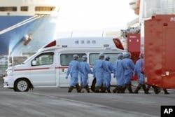 Members of Japan Self Defense Forces walk into the quarantined cruise ship Diamond Princess in the Yokohama Port Sunday, Feb. 9, 2020, in Yokohama, Japan.