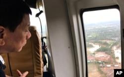 FILE - Philippine President Rodrigo Duterte looks at damage after Tropical Storm Kai-Tak hit the island province of Biliran, central Philippines, Dec. 18, 2017.