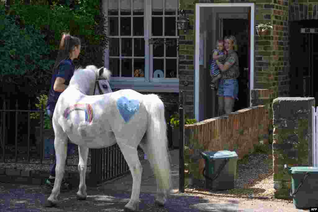"Bryony Blant holding her daughter Alice, who celebrates her 2nd birthday, look at Welsh mountain pony Annie's Wizz held by handler Daisy Cinque outside their home in Twickenham, south west London. Park Lane Stables are taking the fun to peoples' windows during the novel coronavirus lockdown in an initiative called ""Tiny pony at your window."""