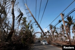 FILE PHOTO: Cars drive under a partially collapsed utility pole, after the island was hit by Hurricane Maria in September, in Naguabo, Puerto Rico, Oct. 20, 2017.