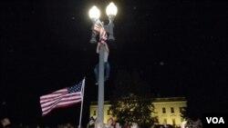 La multitud se reunió a celebrar frente a la Casa Blanca, donde algunos intrépidos se subieron a las columnas de luz para elevar la bandera más alto.