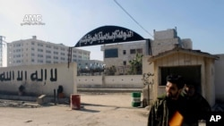 A Syrian rebel stands at the entrance to the headquarters of the Islamic State of Iraq and the Levant, after it fall to the Syrian rebels, in Aleppo, Syria, Wednesday Jan. 8, 2014 (AP Photo/Aleppo Media Center, AMC)