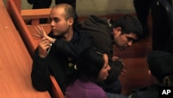 Juan Flores, left, waves to an unidentified person in the back of the courtroom as he sits handcuffed alongside fellow suspects Guillermo Duran, top right, and Nataly Casanova during their hearing in Santiago, Chile, Sept. 23, 2014.