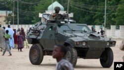 Nigerian soldiers ride on an armored personnel carrier in an area of Nigeria where an Islamic insurgency is raging, in Maiduguri, Nigeria, Aug. 8, 2013.