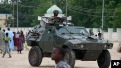 Nigerian soldiers ride on an armored personnel carrier in an area of Nigeria where an Islamic insurgency is raging, August 8, 2013.