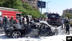This photo released by the Syrian official news agency SANA, shows Syrian fire fighters extinguishing burning cars after a car bomb exploded in the capital's western neighborhood of Mazzeh, in Damascus, Syria, April 29, 2013.