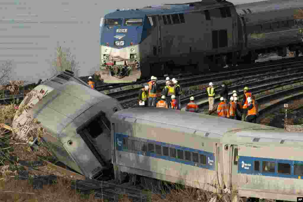 An Amtrak train, top, traveling on an unaffected track, passes a derailed Metro North commuter train in the Bronx borough of New York, Dec. 1, 2013,