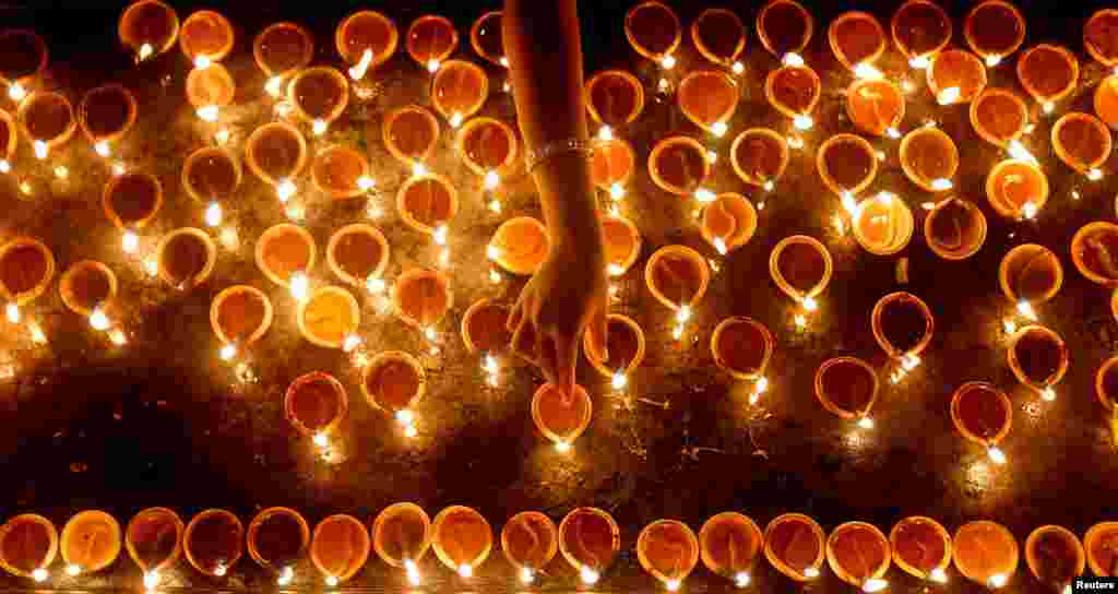 A devotee lights oil lamps at a religious ceremony during the Diwali festival at a Hindu temple in Colombo, Sri Lanka.