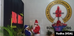 Dua orang muslim berbusana sinterklas dan superhero spiderman berbagi bingkisan Natal untuk anak-anak jemaat Gereja di Solo, Selasa (24/12). Foto : VOA/Yudha Satriawan