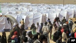 Migrant workers who used to work in Libya and fled the recent unrest in the country, are seen in a refugee camp at the Tunisia-Libyan border, in Ras Ajdir, Tunisia, March 9, 2011,. (AP Image)