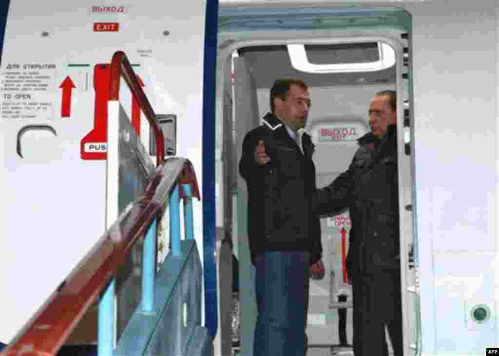 Italian Prime Minister Silvio Berlusconi, right, and Russian President Dmitry Medvedev, back, examine a new Russian passenger plane, Sukhoi Superjet 100, at the airport in the Black Sea resort of Sochi, southern Russia, Friday, Dec. 3, 2010. Italian