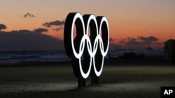 FILE - Olympic rings are placed at the beach before sunrise in Gangneung, South Korea, Jan. 24, 2018.